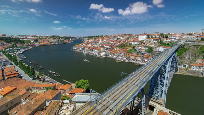 View over red roofs of the historic city of Porto, Portugal with the Dom Luiz bridge timelapse with blue cloudy sky. A metro train can be seen on the bridge | Shutterstock HD Video #13358966