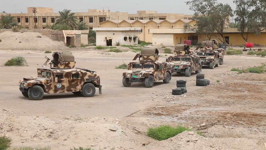 CIRCA 2010s - A convoy of military vehicles moves through a destroyed region of Iraq.