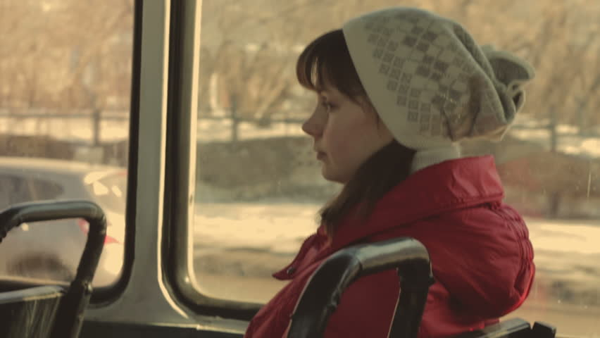 Girl rides on the Tram. Young girl in a red jacket and hat looking out the window. In the sweeps a bright sunny day. Shaking tram gives the dynamics of the video.