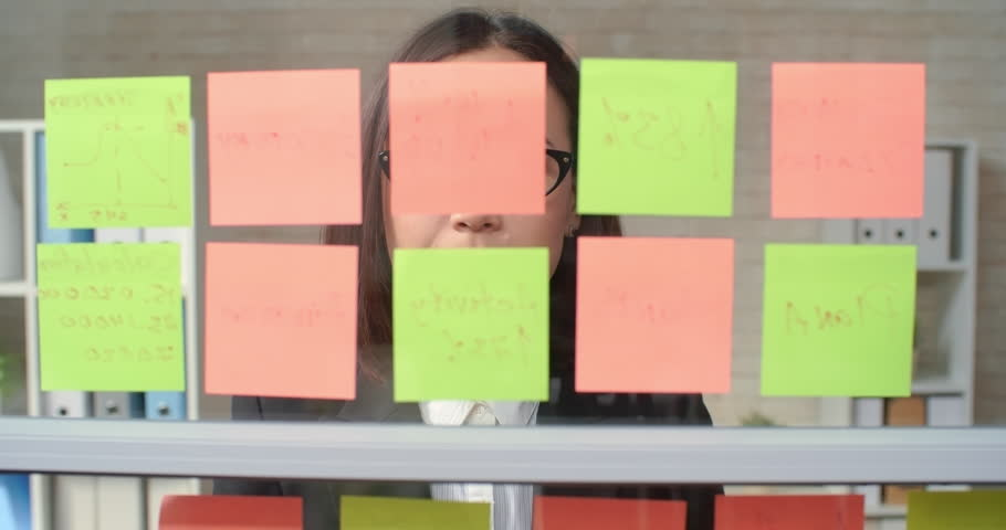 Young businesswoman reading sticky note reminders and removing them from glass wall  | Shutterstock HD Video #13454483