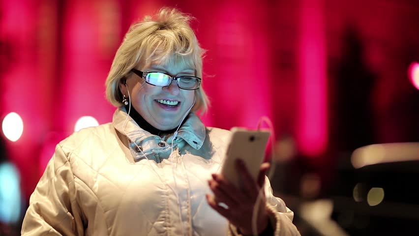 Senior woman standing near the road in nighttime and communicates via smartphone. Cheerful blonde woman with glasses standing near the road and talks in video chat on the mobile phone, she say hello