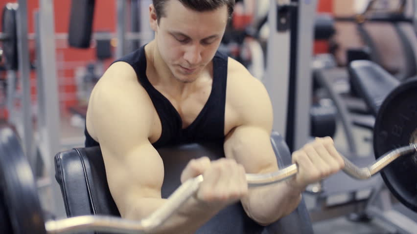 Man working his arms at gym,lifting the dumbbells  | Shutterstock HD Video #13472330