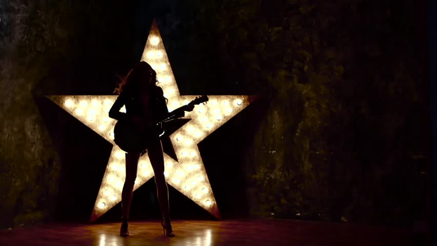 Beautiful sexy girl playing electric guitar in the music hall, shining star in the background. slow motion, silhouette, Attractive steam punk, Portrait of female rock singer, music hall, the scene