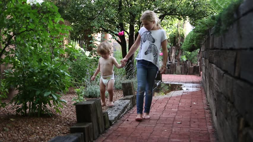 9 year old girl and 2 year old toddler boy walking on patio - HD stock video clip