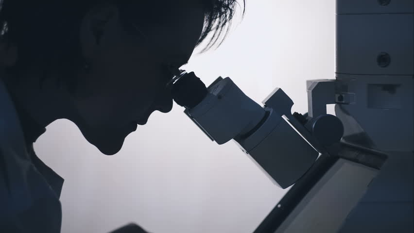 Silhouette of a female researcher looking through a microscope. | Shutterstock HD Video #13597079