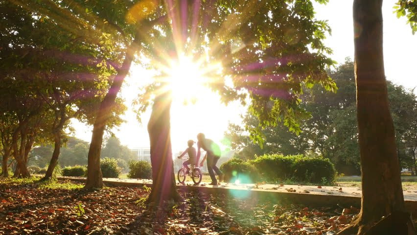 Asian daughter practice to ride a bicycle with her father #13625276
