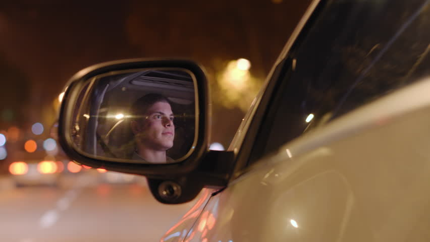 Young male driver is reflected in left side mirror of the moving car. Background is defocused. | Shutterstock HD Video #13644329