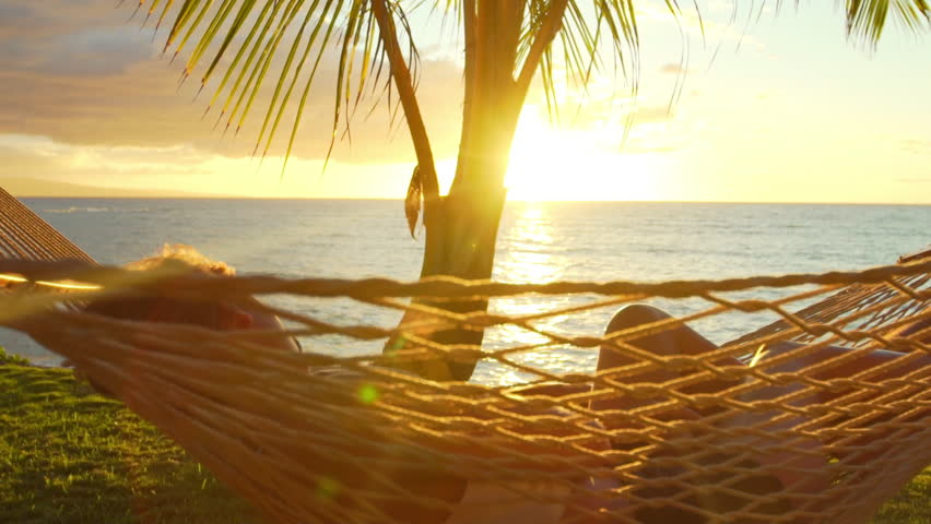Romantic couple relaxing in tropical hammock at sunset. Summer Luxury Vacation.