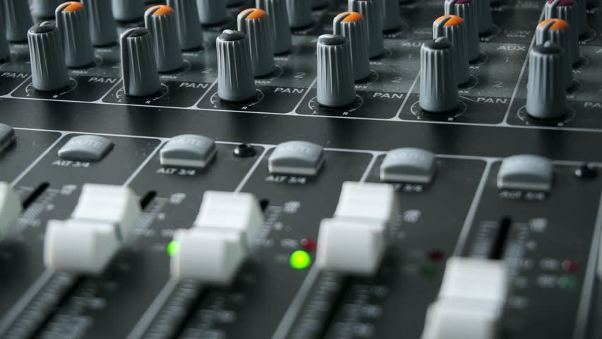 A mixing desk or mixing console being used to mix a track in a recording studio. With level and overload lights, faders and pots / knobs. Focus on the pan pots in this clip.