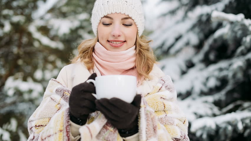 Girl drinks outdoors in winter forest - HD stock footage clip