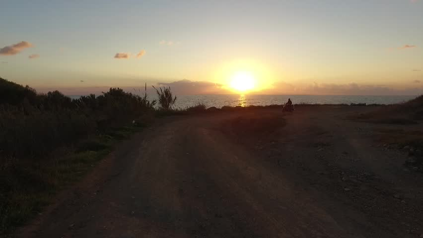 Horizontal focus of the sunset, the sun is bright yellow with orange color, pink sky blue, a little debris in the sky, a quiet sea, around dry grass and bushes man passing by on a moped retro black.   Shutterstock HD Video #13737812