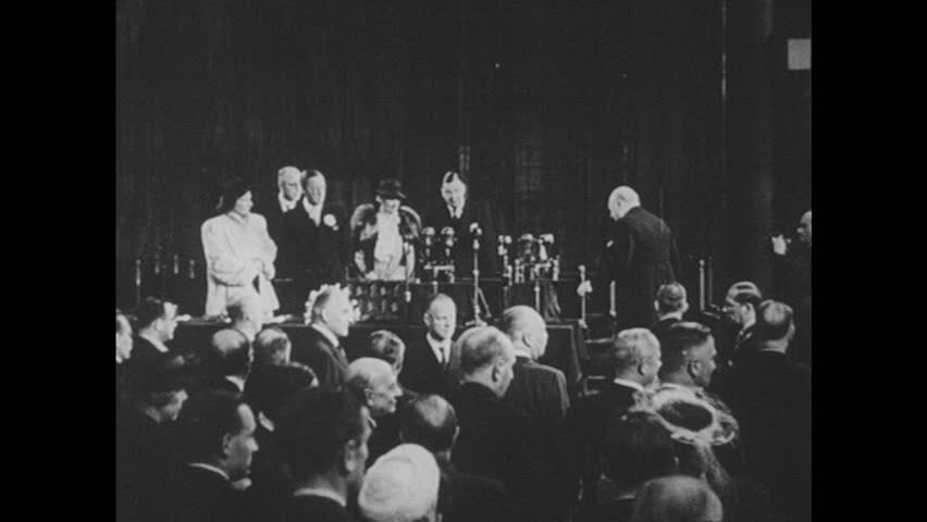 UNITED STATES 1940s: Long shot, Winston Churchill on stage / Churchill speaking at podium / Wipe to George Bernard Shaw outside of house.