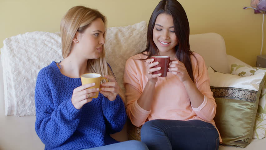 Two pretty young women enjoy a relaxing coffee - HD stock footage clip