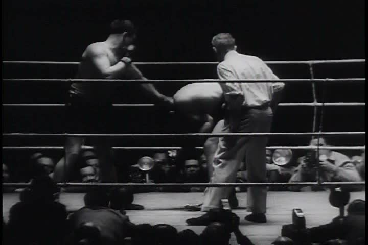 CIRCA 1970s - Two men fight until one falls as part of a box match in a ring in the 1970s. - SD stock video clip