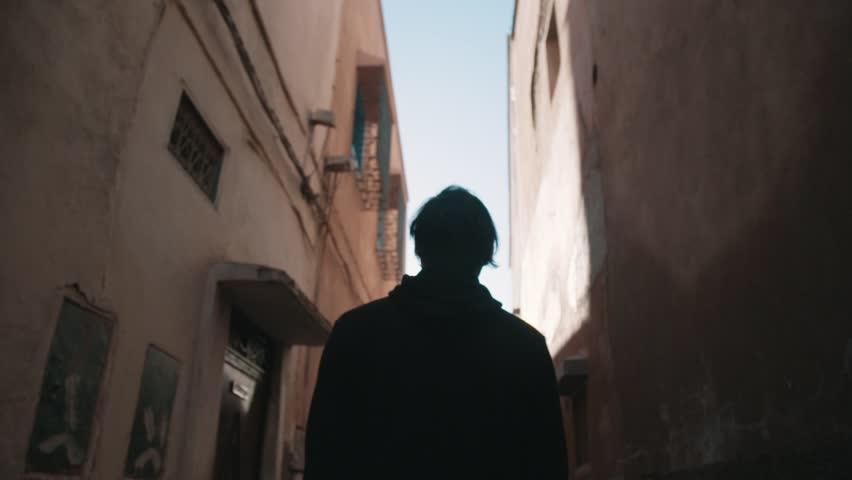 Figure walking through a tight Moroccan alley way