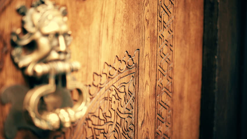 Focus pull over ancient wooden door on hand knocker. Hand opens doors. Wooden carved door with bronze hand knocker. UHD | Shutterstock HD Video #13962839