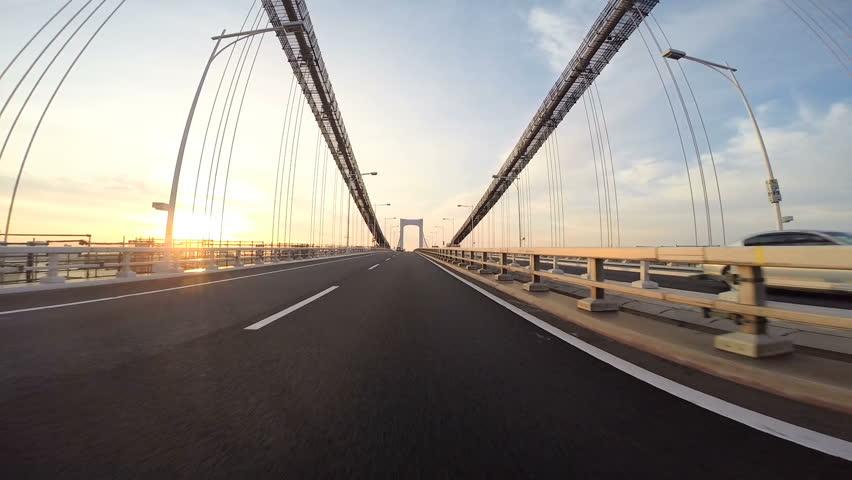 Driver's point of view across the bridge towards the climbing sunshine over the city horizon. Part 2. Tokyo Rainbow Bridge eastbound towards Odaiba.