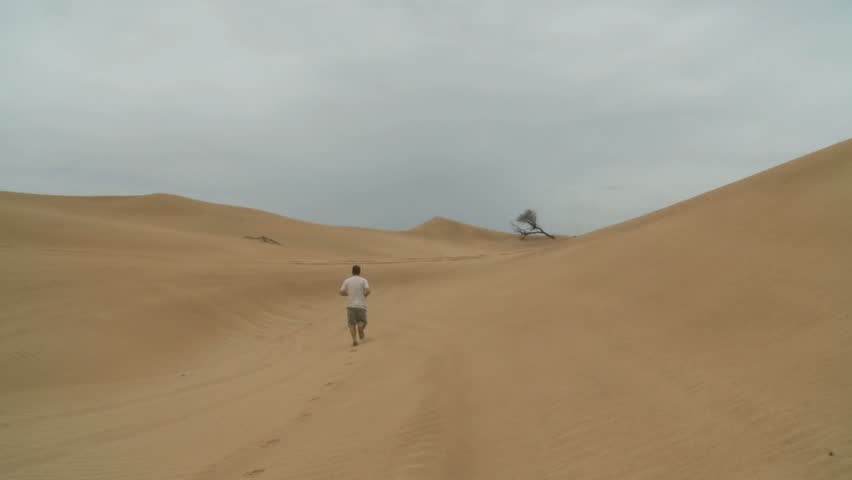 Man walking in the middle of the desert. Abu Dhabi is the capital and the second largest city of the United Arab Emirates. Abu Dhabi. May 2013 - HD stock footage clip