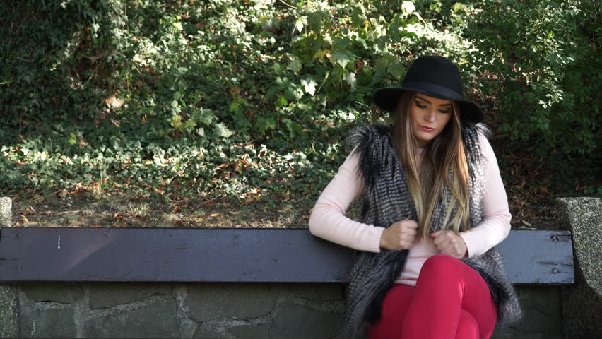 Woman outdoor. Fashionable autumn girl long hair wearing fur vest black hat waiting for someone sitting on bench in park watching her watch 4K, Prores HQ codec - 4K stock video clip