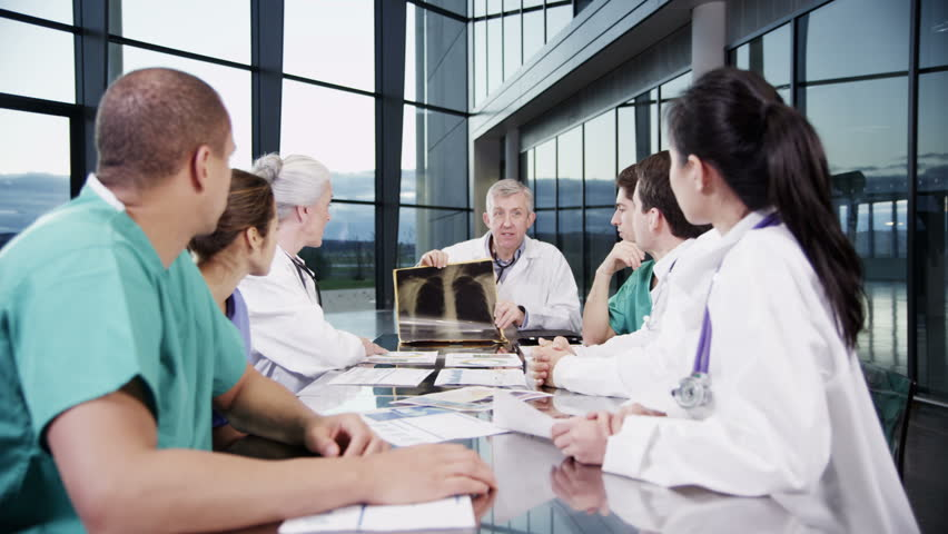 4k / Ultra HD version A diverse team of medical personnel are having a meeting in a light, modern private healthcare facility. They are discussing x-rays and looking for a diagnosis. In slow motion.  | Shutterstock HD Video #14127359