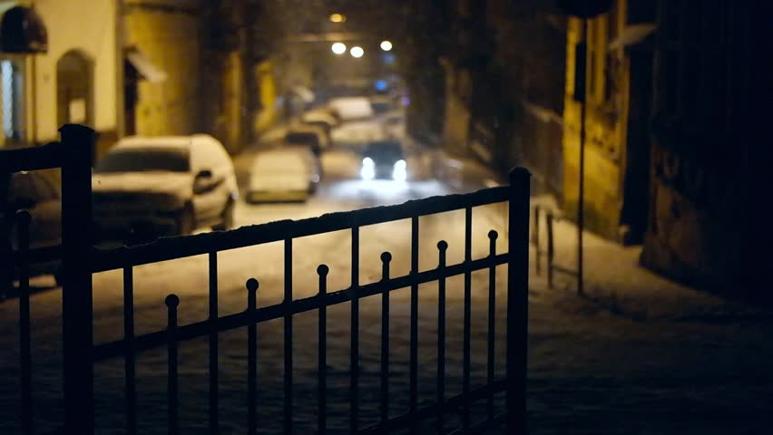 Out of focus car lights at snowing street in night. Slow motion - HD stock footage clip