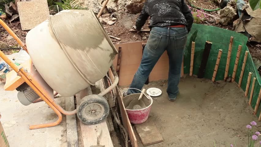 Video clip of mason reinforcing the fresh cement during the construction of artificial pond in the garden.