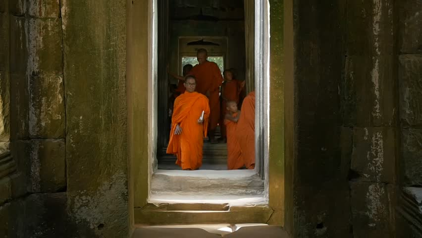 ANGKOR WAT, CAMBODIA - NOV 2015: Buddhist monk walking in temple. Slow motion orange robe buddhist monk walking in temple of Angkor Wat Cambodia ancient ruin of religious temple to meditate. - HD stock video clip