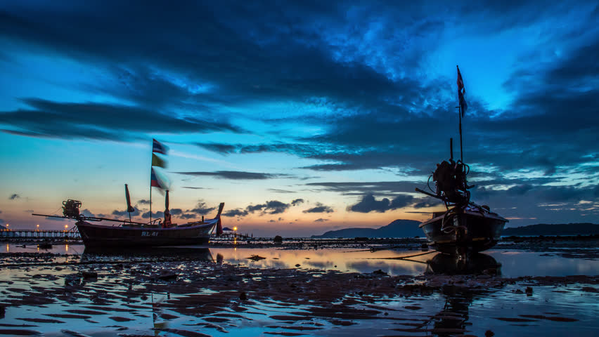 Timelapse of the beautiful sunrise with long-tail boats in low water during high tide,Thailand. January, 2016. - 4K stock footage clip