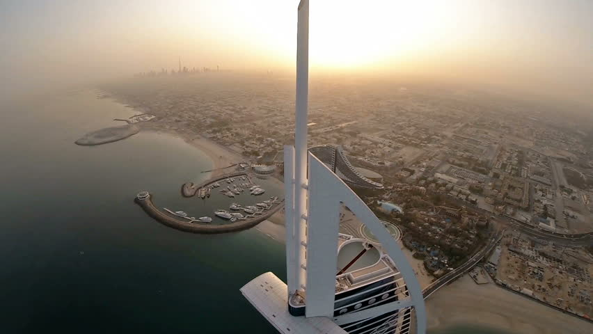Fly over Burj Al Arab hotel in Dubai, UAE. Burj Al Arab is a luxury 5 star hotel built on an artificial island in front of Jumeirah beach. Helicopter aerial view at sunrise