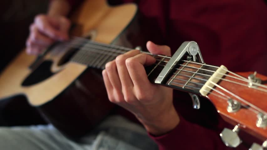 Young Man's Hands Playing The Acoustic Guitar. A Young Man ...