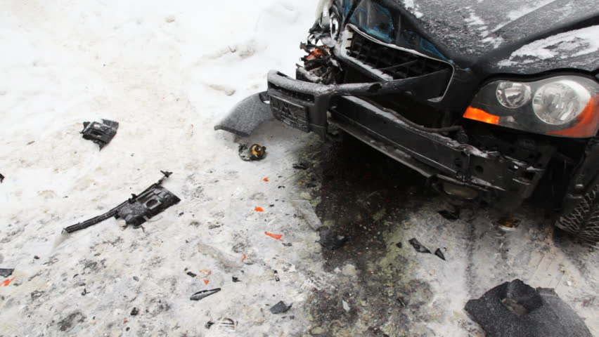 strongly battered car is on icy road with flashing emergency lights and around wreckage