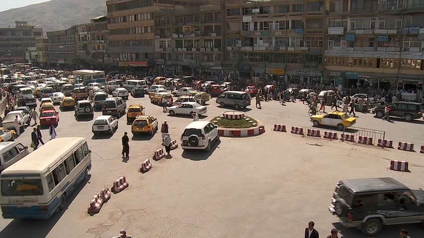 A wide establishing shot of downtown Kabul, Afghanistan with bus, taxi and vehicle traffic. - SD stock video clip