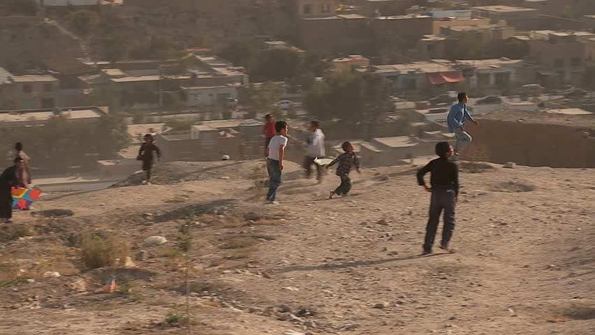 KABUL, AFGHANISTAN - CIRCA 2009: Boys play on the hillsides flying kites in modern circa 2009 in Kabul, Afghanistan. Afghanistan is an impoverished and least developed country, one of the world's poorest.  - SD stock video clip
