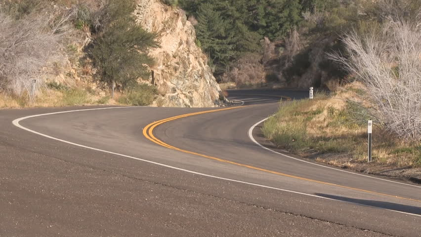 Modern grey car accelerates off of shoulder onto scenic mountain road (HD with audio).