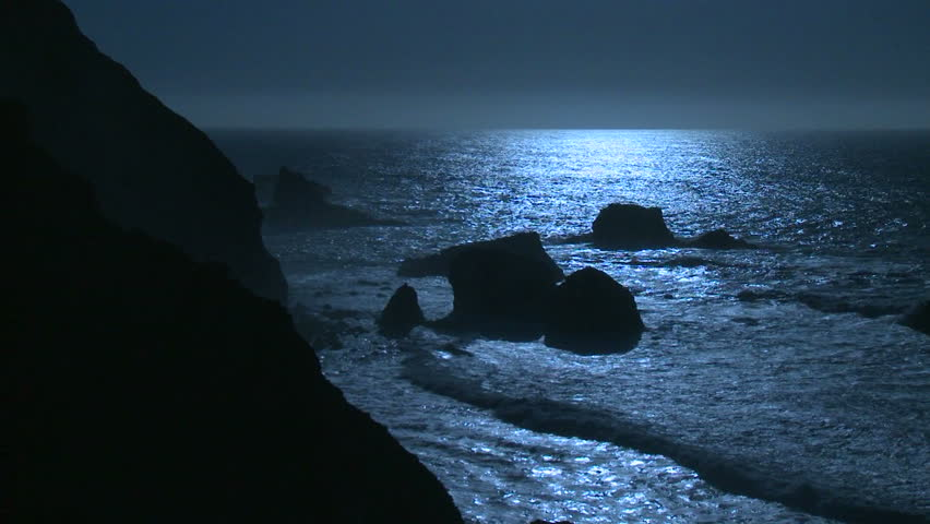 Surf rolls into the Big Sur Coastline of California under a full moon effect. - HD stock footage clip