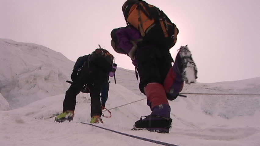 The sun beats down on climbers as they ascend icy slope - SD stock video clip
