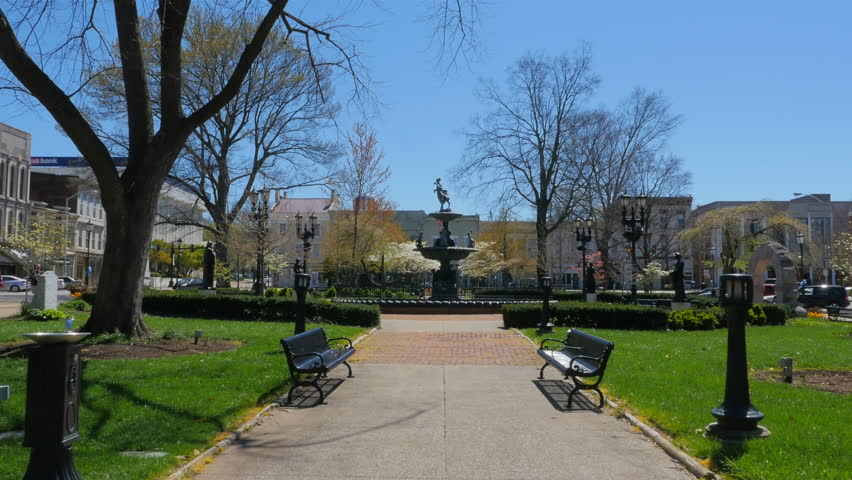A dolly shot of beautiful Public Fountain Square in early Spring in downtown Bowling Green Kentucky with luscious vivid green grass, park benches and flowering trees.  But, no running fountain.