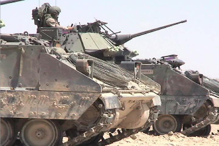 A line of American army tanks sits awaiting combat operations in the Iraqi desert.