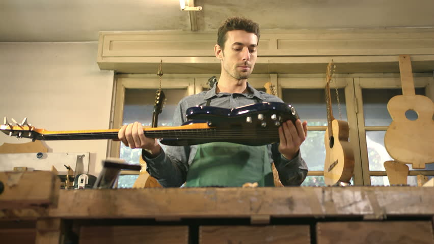 People and art, adult man at work as artisan in italian workshop with bass guitar and musical instruments, craftsman atelier - HD stock video clip
