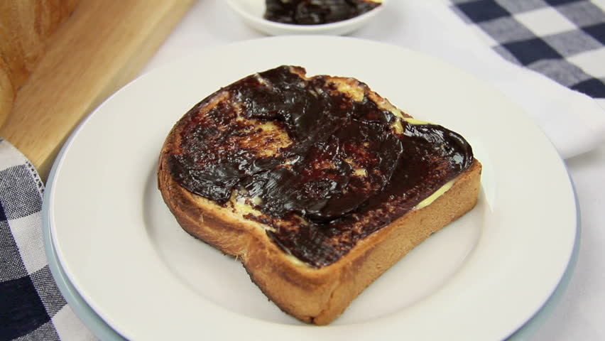 Australian flag being put in a piece of toast with butter and vegemite.