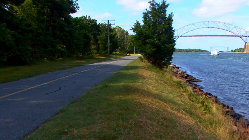 Beautiful sunny day at Cape Cod canal showing tour boat, Bourne & distant train bridge and couple walking their dog on path