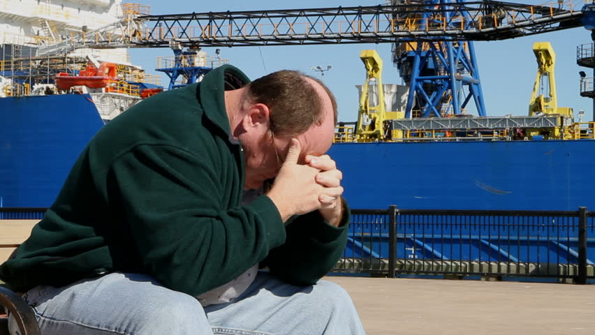 Depressed unemployed man sits on a bench at the shipyard with his head in his hands. - HD stock video clip