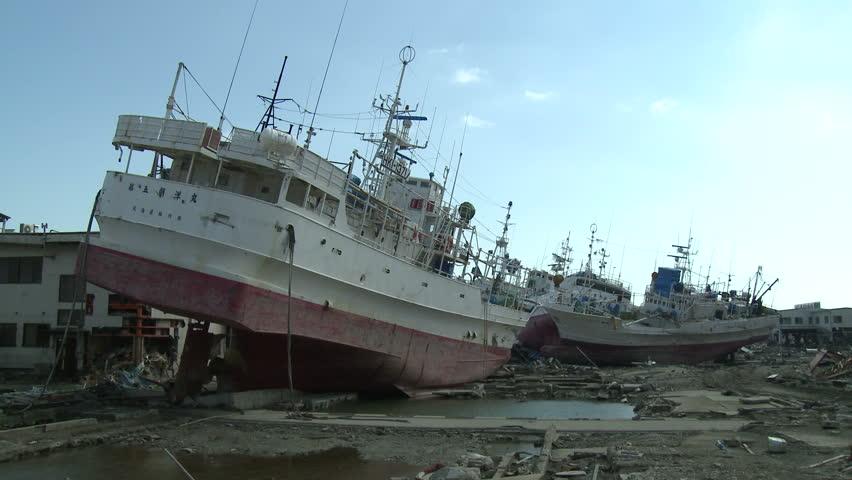 KESENNUMA, JAPAN - CIRCA APRIL 2011: Ships rest inland in tsunami stricken port in Kesennuma, Japan circa April 2011.