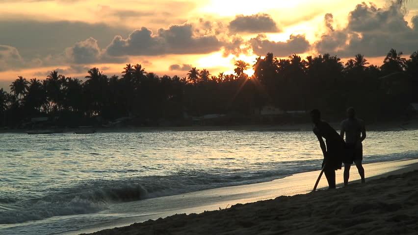 UNAWATUNA, SRI LANKA - NOV 15, 2006: Two guys play cricket on Unawatuna Beach in Sri Lanka. - HD stock video clip