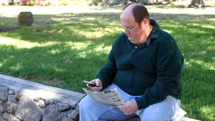 Unemployed obese man uses a cell phone to call about a job in the want ads section of the newspaper while in the park. - HD stock video clip