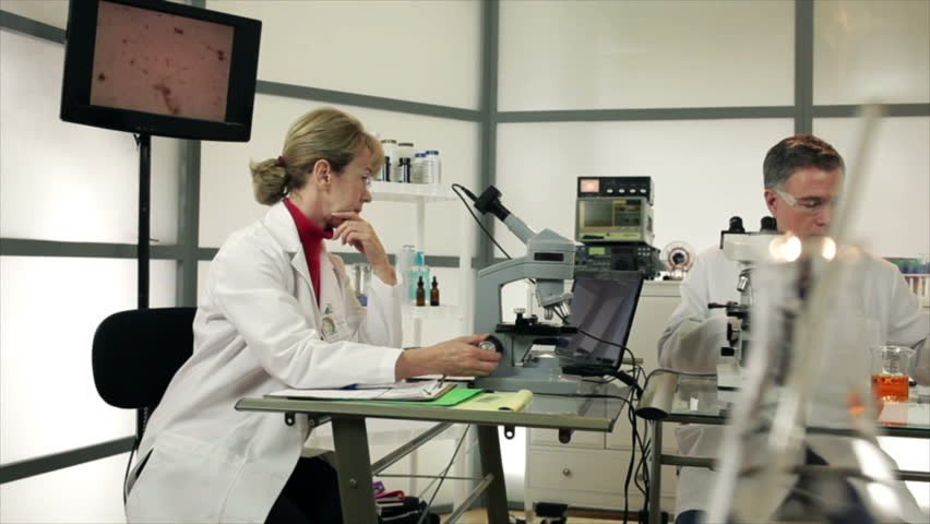 A male lab tech using a Pipette and a female researcher with a microscope camera working together in a laboratory setting. Slow dolly movement past colorful objects in the foreground. - HD stock video clip