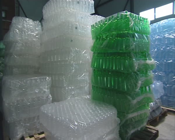 Piles of packaged PET bottles in warehouse. Industrial plastic recycling factory.