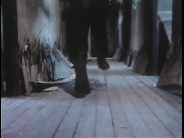 Rear view of men running down hallway