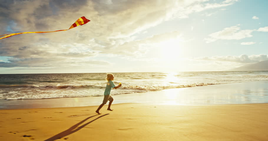 Young boy playing with kite on the beach | Shutterstock HD Video #18597380