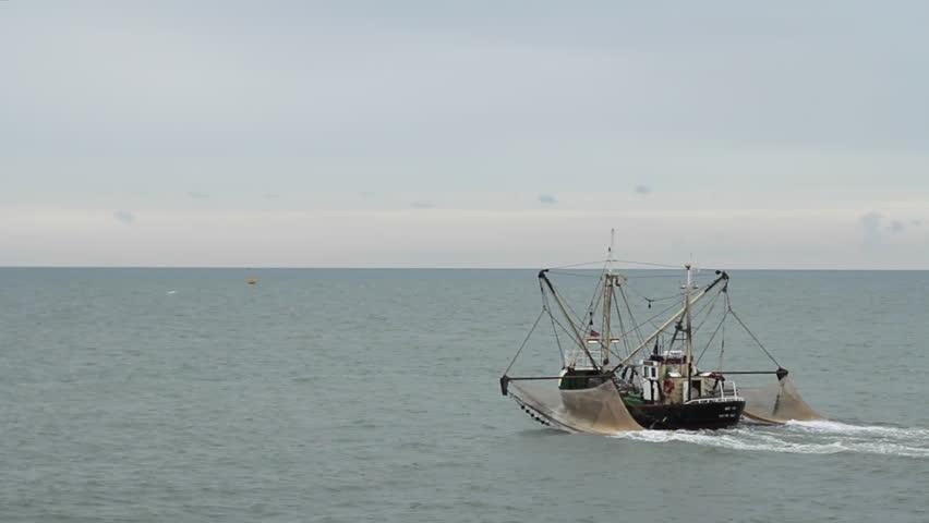 WIDE ungraded shot of shrimp fishing boat moving towards the horizon